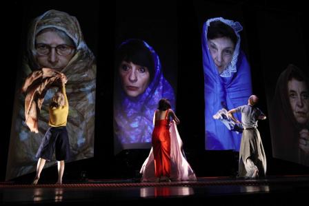【プログラム公式写真。布を魔女ないし民族衣装風にまとった母親の映像に、子どもたちが向かい合う。photo: Doro Tuch、提供=KYOTO EXPERIMENT 禁無断転載】