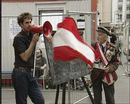 【プロジェクトの初日に現れた老人。まるで化石である。国旗を掲げてシュリンゲンジーフ(左)に迫る。クレジット:Christoph Schlingensief in AUSLÄNDER RAUS by Paul Poet_Copyright Filmgalerie 451】