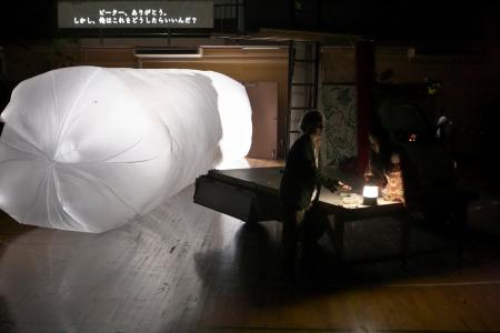 【「永い遠足」公演より。大きな白いポリ袋はピーターの「新しい国」を表す。右側の2人はノブオとアイカ(青木司撮影。提供=サンプル。禁無断転載)】