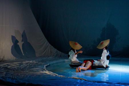 【リハーサルから。目黑大路の身体を小舟に見立て、お盆を挟んで座った柏木と梶村が連想ゲームをする。撮影:井上嘉和、提供=KYOTO EXPERIMENT 禁無断転載】